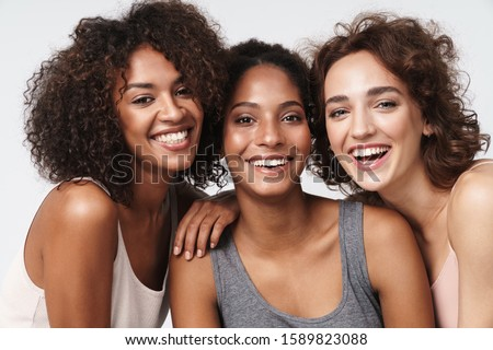 Portrait of three young multiracial women standing together and smiling at camera isolated over white background #1589823088