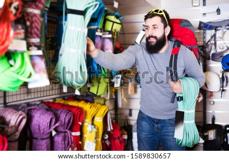 Young man choosing climbing equipment in sports equipment shop #1589830657