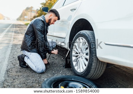 Bearded man, mechanic changing tire that are his car. #1589854000