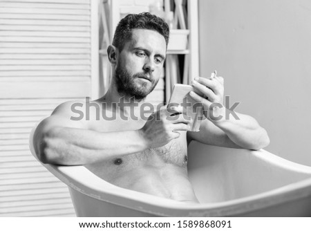 Relaxed guy reading book while relaxing in hot bath. Relax at home. Total relaxation. Personal hygiene. Nervous system benefit bathing. Relax concept. Man muscular torso relax bathtub and read book. #1589868091