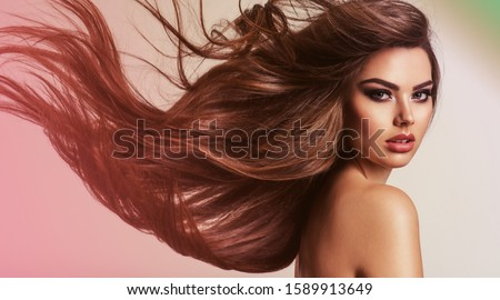 Portrait of a beautiful woman with a long hair. Young  brunette model with  beautiful hair - isolated on white background. Young girl with hair flying in the wind. #1589913649