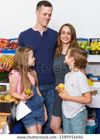 parents with two kids standing near shelves with fruits  in local supermarket  #1589916646