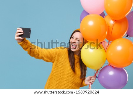 Crazy woman in sweater hat posing isolated on blue background. Birthday holiday party, people emotions concept. Mock up copy space. Celebrating hold air balloons doing selfie shot on mobile phone