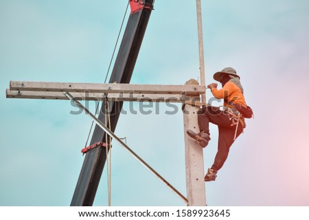 Worker on the height wear safety harness, Electric lineman repairman worker at climbing work on electric post power pole. #1589923645