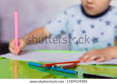Little boy drawing with color pencils. Selective focus on colored pencils.