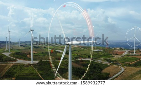 Aerial view of windmills with digitally generated holographic display tech data visualization. Wind power turbines generating clean renewable energy for sustainable development in a green ecologic way #1589932777