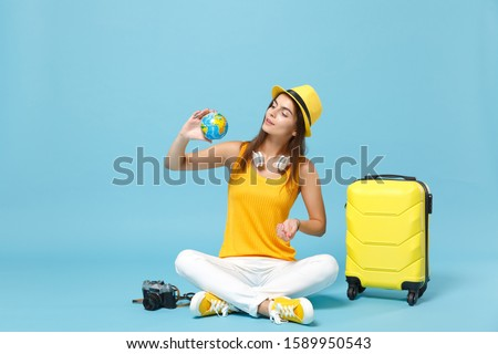 Traveler tourist woman in yellow casual clothes hat with suitcase photo camera isolated on blue background. Female passenger traveling abroad to travel on weekends getaway. Air flight journey concept #1589950543