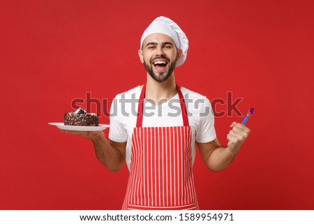 Cheerful male chef cook or baker man in striped apron white t-shirt toque chefs hat posing isolated on red background. Cooking food concept. Mock up copy space. Holding plate with cake, birthday pipe #1589954971