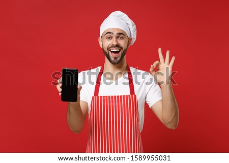 Excited male chef cook or baker man in striped apron toque chefs hat isolated on red background. Cooking food concept. Mock up copy space. Hold mobile phone with blank empty screen showing OK gesture #1589955031
