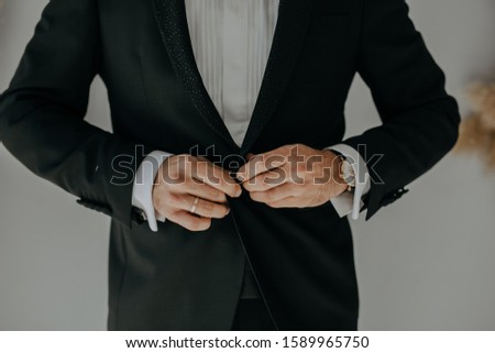 Bridegroom buttoning up his jacket. He is preparing for wedding ceremony. #1589965750