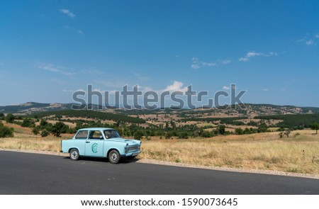 Near Vinica / North Macedonia - 23 August 2019: Side view of a vintage egg shell blue Trabant car parked by the side of the road. Classic car summer holidays through colourful countryside.  #1590073645