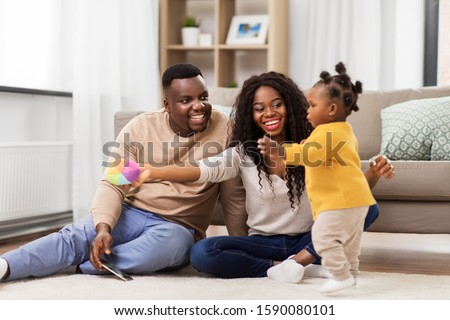 family, parenthood and people concept - happy african american mother and father playing with baby daughter at home #1590080101