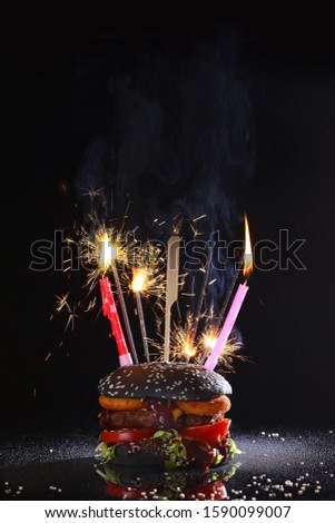 Burger with a black bun decorated with sparklers and candles for the cake.The concept of a new year holiday or for birth. Copy space. Macro photo on a black background. #1590099007