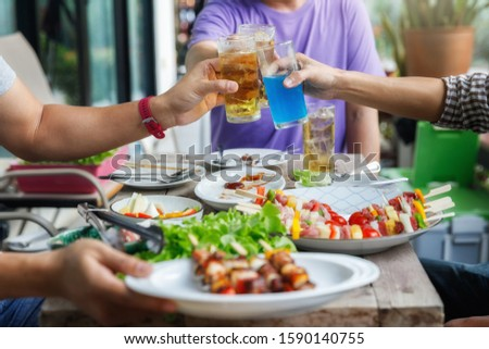 Young men cheers for a drink at a BBQ party between friends. Food, drink, people and family time concept. #1590140755