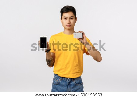 Guy showing how simple download application for entering online banking system, managing finance business with help smartphone, holding mobile phone and credit card, order online, white background