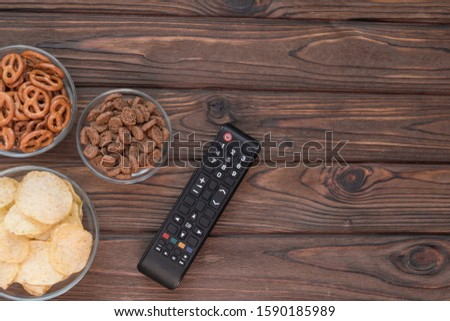 Chips, croutons, snacks. TV remote on the background of a wooden table. leisure. Leisure. #1590185989
