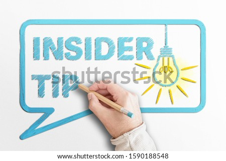 hand holding pencil writing words INSIDER TIP in speech bubble with glowing light bulb #1590188548