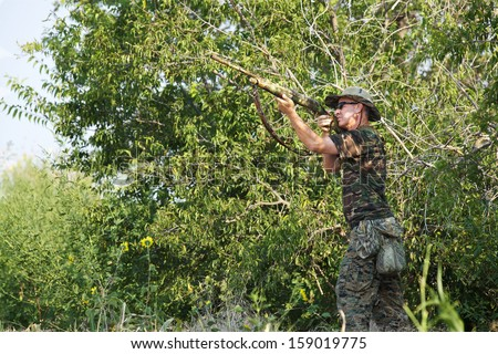 Hunter takes aim while dove hunting.  Horizontal, color, space for copy. #159019775