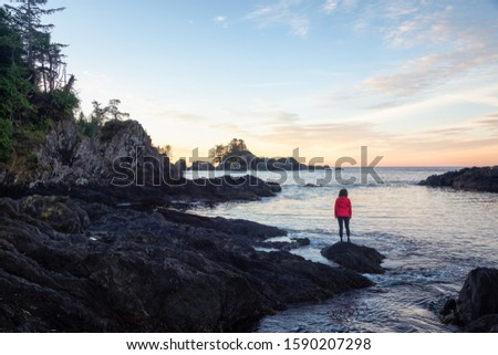 Wild Pacifc Trail, Ucluelet, Vancouver Island, BC, Canada. Adventurous Girl Enjoying the Beautiful View of the Rocky Ocean Coast during a colorful morning sunrise. Concept: Travel, adventure, freedom #1590207298