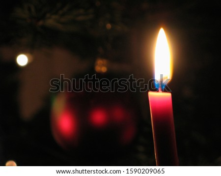Lit candle next to Christmas ornament #1590209065