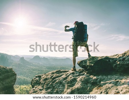 Traveler man looking at mountain view and making landscape photo using smartphone, shinning screen #1590214960