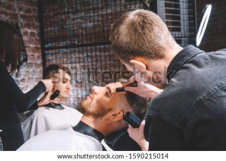 Young male barber makes a haircut beard client with vintage straight razor. Shaving process of beards in Barbershop #1590215014