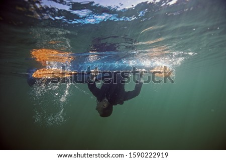 Underwater shot of person upside down in kayak
