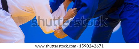 Two judo fighters in white and blue uniform. Martial arts competition - sambo, judo, karate, jiu jitsu, wrestling Royalty-Free Stock Photo #1590242671