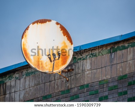 Round shape damaged rusty satellite antenna on grey building wall background and blue skies in above. Geometric variations and abandoned communications concept #1590309739