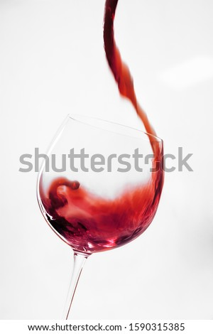 Red wine pouring into glass #1590315385