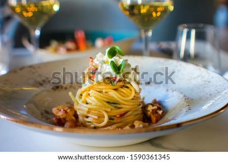 haute cuisine dish with spaghetti with lobster, buffalo stracciatella and a fine white wine. In a luxurious Italian restaurant Royalty-Free Stock Photo #1590361345
