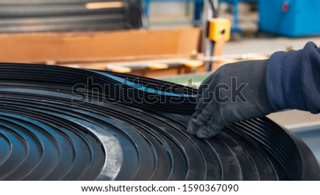 wrapped rubber profile being checked on Foreman's side Royalty-Free Stock Photo #1590367090