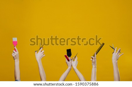 Three sets of woman hands in the air holding hairdresser tools, such as brushes, scissors and combs over yellow backgound. Cropped. Hands only. #1590375886