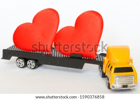 The truck carries hearts for Valentine's Day or likes for users of social networks. Celebration, symbolism and generally accepted signs. To texts about the holiday or about sites on the Internet #1590376858