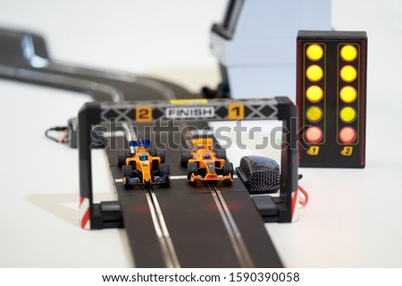 Race car racing on a race track. Toy Kart crossing the finish line with traffic lights #1590390058