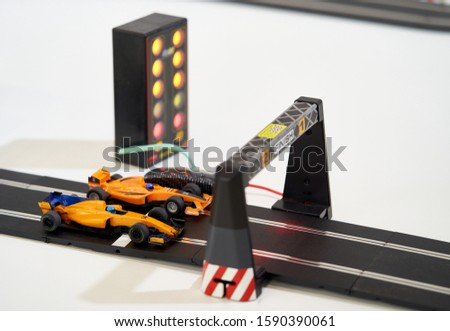 Race car racing on a race track. Toy Kart crossing the finish line with traffic lights #1590390061