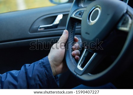 Male driver hands holding steering wheel #1590407227