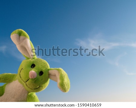 cheerful easter bunny looks round the corner, blue sky in the background