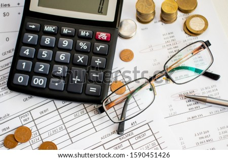 A finance still life with a jar of Sterling coins on Sterling notes, calculator and pen. #1590451426