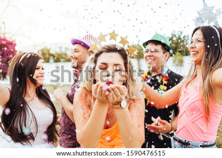 Brazilian Carnival. Young woman in costume enjoying the carnival party blowing confetti #1590476515