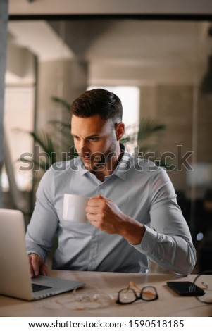 Businessman working on his laptop. Executive manager drinking coffee and working on his computer. Young manager relaxing and working on his computer. #1590518185