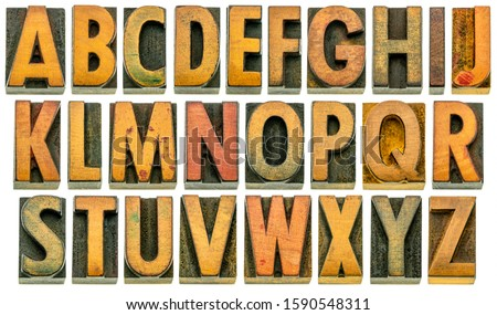 English alphabet in wood type - 26 isolated letters in letterpress printing blocks with a lot of character due to scratches and ink stain, shot at slight angle for 3D effect Royalty-Free Stock Photo #1590548311