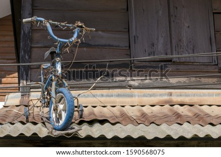 Vintage bicycle On a vintage roof And the background of the vintage wooden house #1590568075