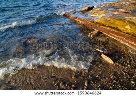 Rocks abound on the sandy Lake Superior Shore at Hurricane River Beach in Pictured Rocks National Lakeshore in Alger County, Michigan