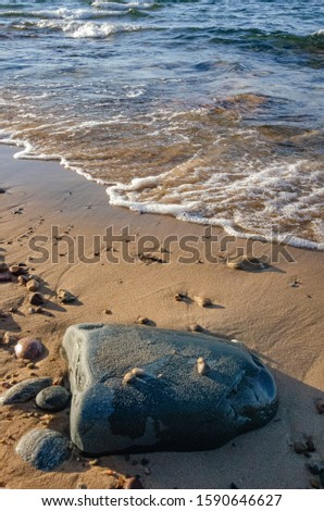 Rocks dot the sandy Lake Superior Shore at Hurricane River Beach in Pictured Rocks National Lakeshore in Alger County, Michigan