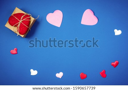 Red heart with a gift to Valentine's Day on a beautiful blue background. Heart pendant. Space for text. Red heart. Valentine Day. #1590657739