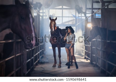 Beautiful woman in cowgirl concept standing with horses in barn house