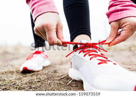 Woman runner tying sport shoes. Walking or running legs, autumn adventure and exercising outdoors. Motivation and inspiration fitness concept outside. Royalty-Free Stock Photo #159073559