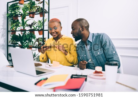 Young African American woman taking photo of piece of cake with smartphone for sharing in social media while working with male colleague in cafeteria #1590751981