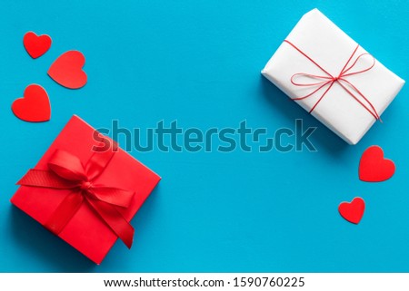 Present to a lover on Valentine's Day. Gift boxes near paper hearts on blue background top-down frame copy space #1590760225